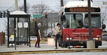 Gwinnett County Transit buses take on passengers at a bus stop on Satellite Road in Duluth in this 2012 photograph. County commissioners voted this week to spend .6 million to replace the system's 28 local service buses because of old age and high mileage. (File Photo)