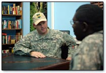 military man talking with another man while sitting at a table
